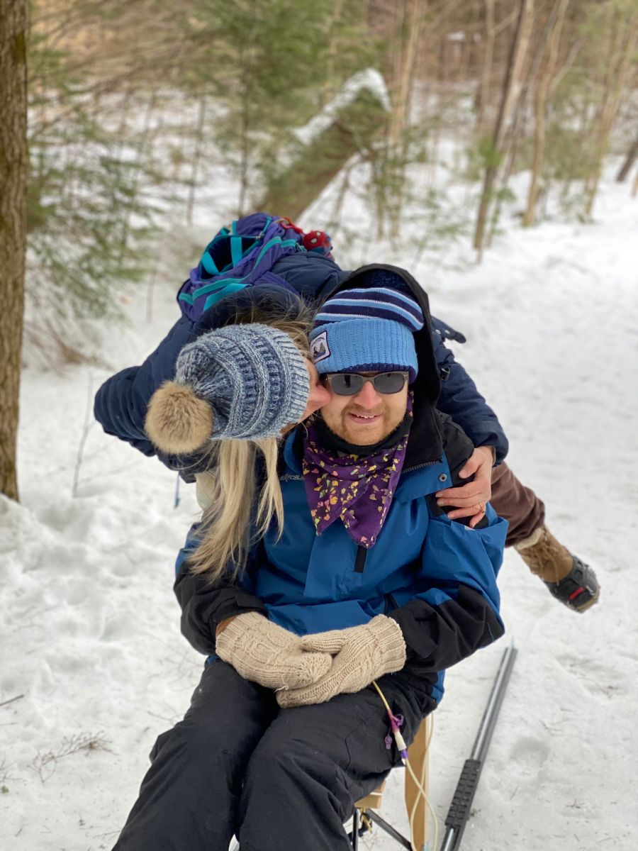 On a snowy trail, a woman wearing a backpack leans down to kiss a young man on his cheek.  The young man is smiling and seated on a kicksled.