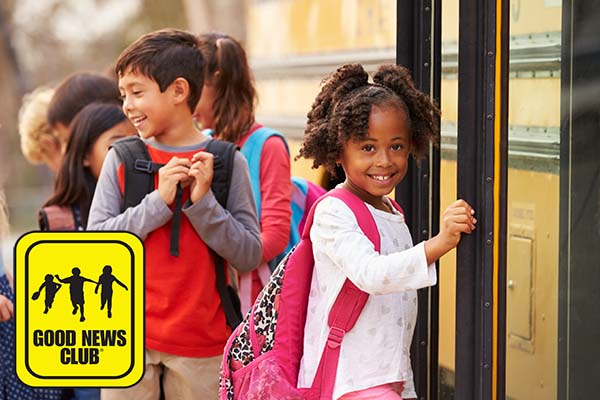 Child in line at school bus with GNC logo