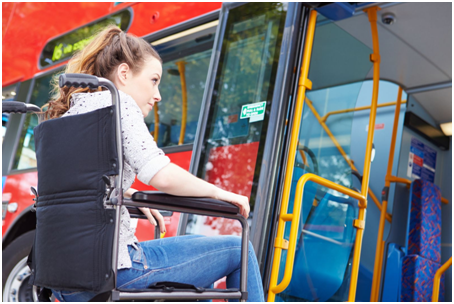 Young woman on wheelchair boarding a bus