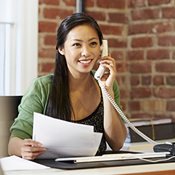 Asian woman on phone holding papers in an office