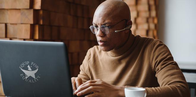 Black man typing on laptop at coffee shop