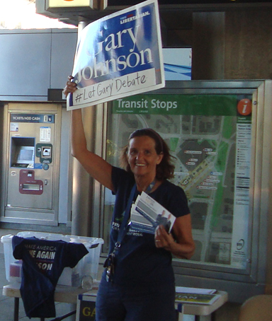 Young woman waving a Gary Johnson for President sign at BART station (color photo)