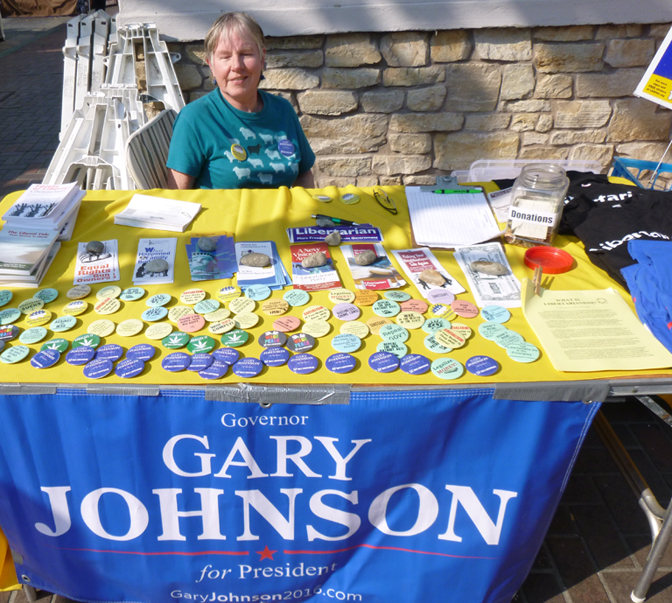 Jane Heider seated at LP table outdoors promoting Johson for President (photo)