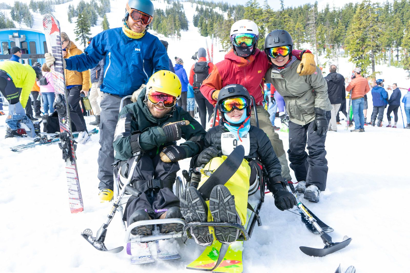 Sit-ski athletes Gabe (left) and Ken (right) with family and friends behind them