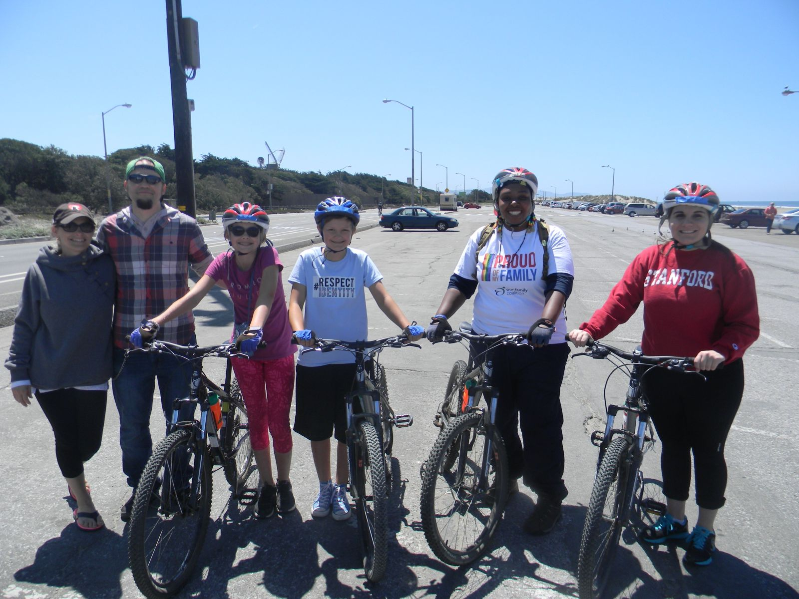 Kids and adults on bikes pose and smile. It's sunny and next to a beach.