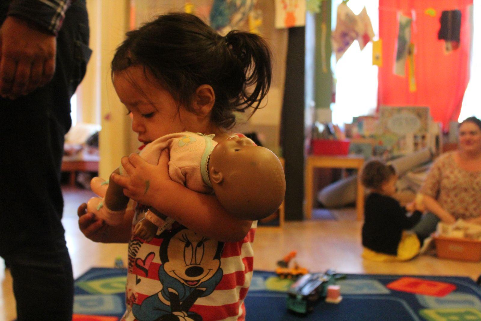 Little girl holding baby doll