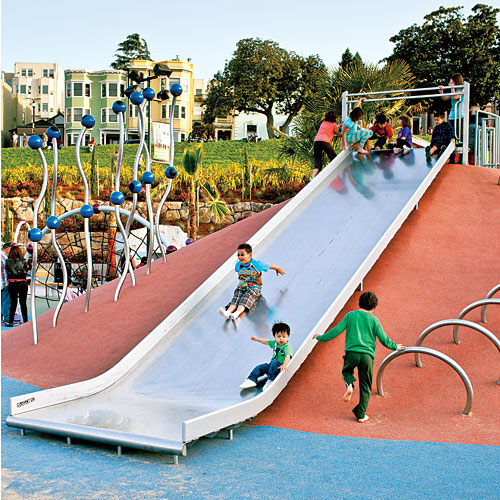 Kids go down a giant slide at a whimsical-looking playground.