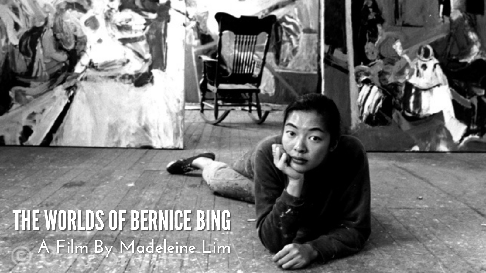 A black and white photo of Bernice Bing, an Asian American woman with black hair, as she lounges on her stomach on the wood-paneled floor and looks into the camera. Behind her, a large rocking chair sits empty between large abstract paintings that lean against the wall.