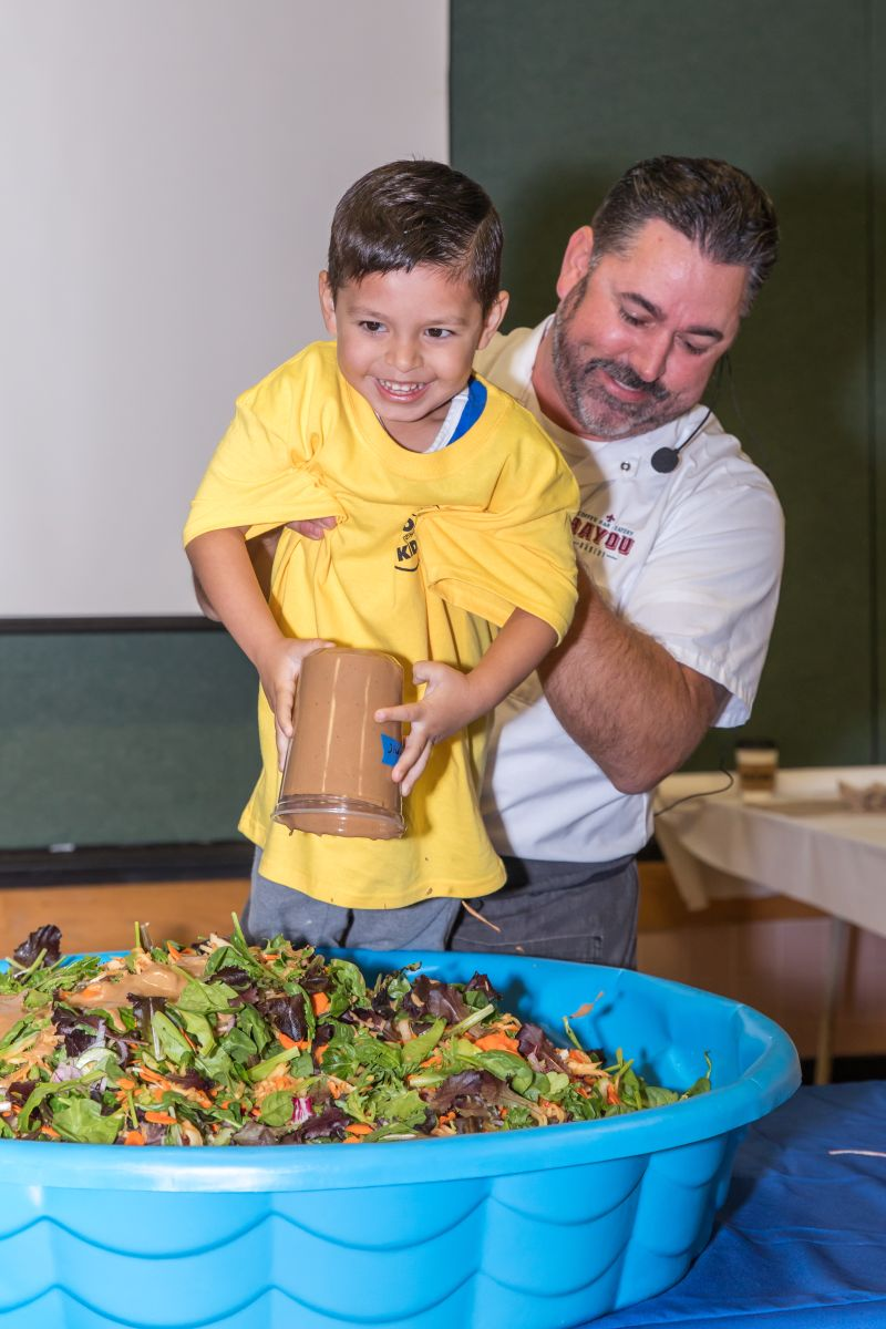 Chef David Guas gives a young helper an assist at Real Food for Kids 2018 Food Day event.