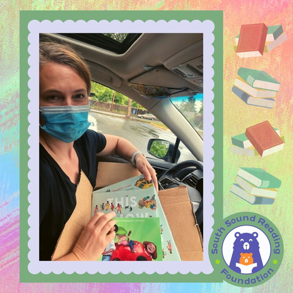 White woman in blue face mask holding box of books in car