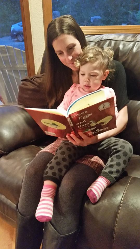 Brunette caucasian woman sitting on brown leather couch reading Green Eggs and Ham with a light brown haired caucasian toddler in lap.