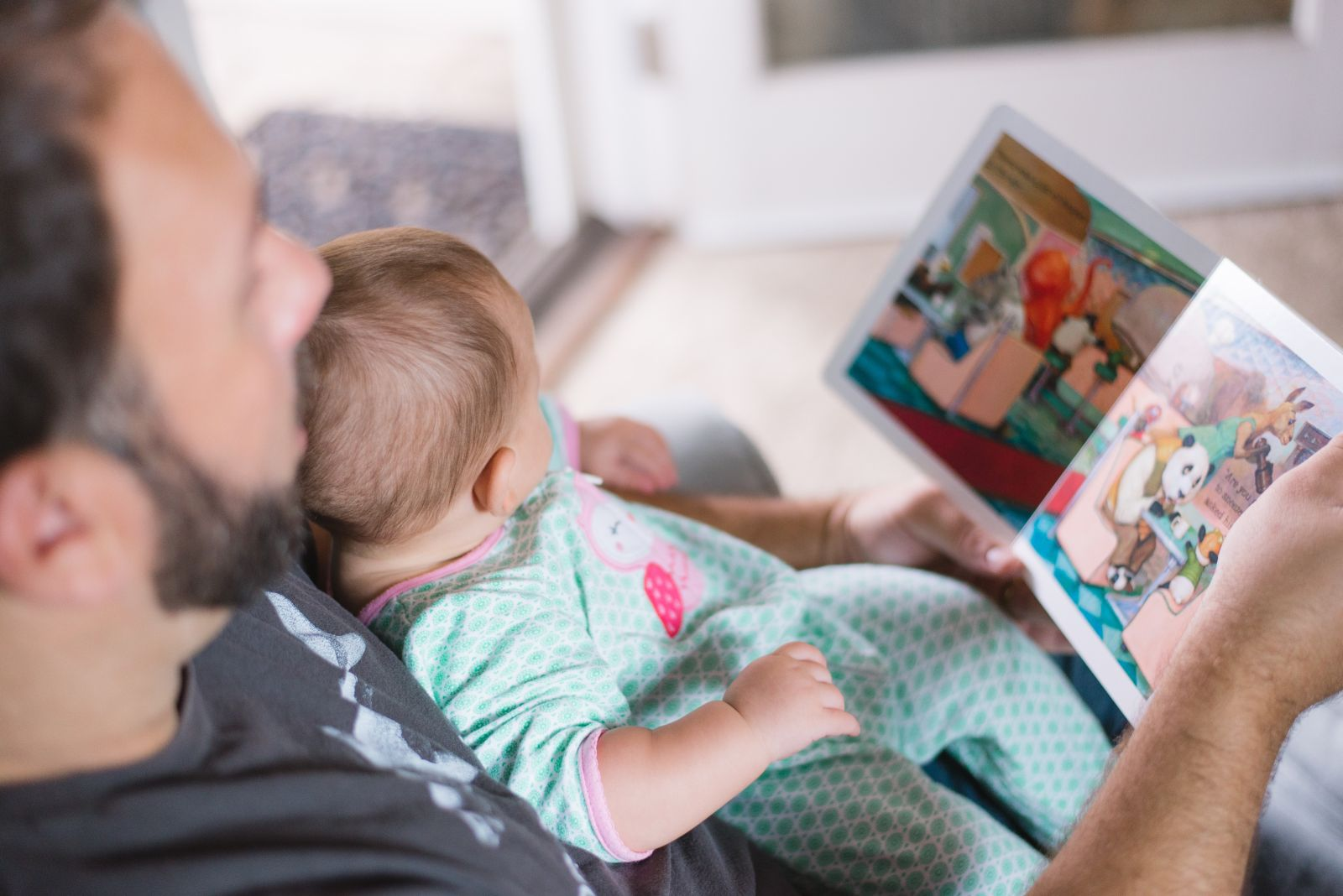 Man with infant sitting in his lap, leaning against his chest. Man is holding up book with colorful photos and both of them are looking down at pictures.